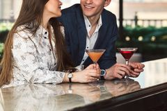 Man and woman enjoy the conversation on a date on bar counter drinking cocktails. Man and women enjoy the conversation on a date on bar counter drinking royalty free stock images