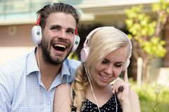 Man with woman enjoy music outdoor with urban background, defocused royalty free stock images