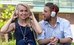 Man with woman enjoy music outdoor with urban background, defocused. Man with women enjoy music outdoor with urban background, defocused. Music and technologies Stock Images