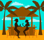 Man and woman enjoy summer vacation, drink cocktails at beach bar, silhouettes. Scene Royalty Free Stock Photo