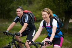 Man and woman enjoying a bike ride in nature Royalty Free Stock Image