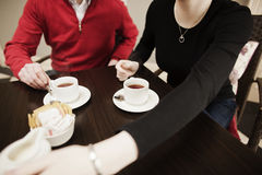 Friends Drinking Coffee Together. A man and woman enjoying cups of coffee together Stock Photos