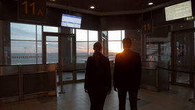 Man and woman enjoying sunset through airport. Slow motion back shot of young man and woman at the airport. They coming closer to window to look at beautiful stock video footage