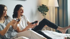 Man and woman enjoying video game having fun at home sitting on bed together. Man and woman beautiful young couple are enjoying video game having fun at home stock video footage