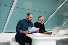 Man and woman entrepreneurs working together on portable net-book in modern office interior Royalty Free Stock Photos