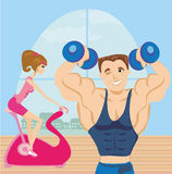 Man and woman exercises in the gym Stock Images