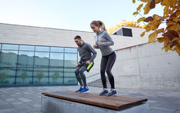 Man and woman exercising on bench outdoors Royalty Free Stock Image