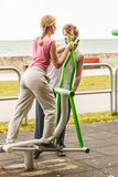 Man and woman exercising on elliptical trainer. Royalty Free Stock Image