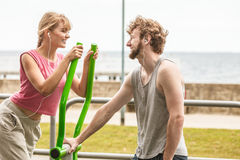 Man and woman exercising on elliptical trainer. Stock Images
