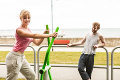Man and woman exercising on elliptical trainer. Stock Image