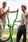Man and woman exercising on elliptical trainer. Stock Photo