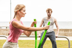 Man and woman exercising on elliptical trainer. Royalty Free Stock Photography