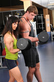 Man and Woman Exercising in Gym Stock Image