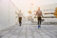 Man and woman exercising with jump-rope outdoors Stock Image