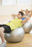Man And Woman Exercising On Pilates At Health Club Royalty Free Stock Images