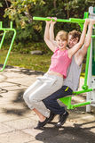 Man and woman exercising on pulldown outdoor. Active young men and women exercising on pulldown machine. Muscular strong guy and girl in training suit working Royalty Free Stock Photo