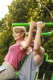 Man and woman exercising on pulldown outdoor. Active young men and women exercising on pulldown machine. Muscular strong guy and girl in training suit working Royalty Free Stock Photography