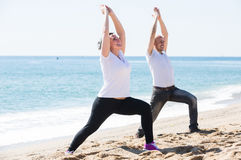 Man and woman exercising together on the beach Royalty Free Stock Photos