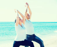 Man and woman exercising together on the beach Stock Image