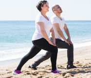 Man and woman exercising together on the beach Stock Photo
