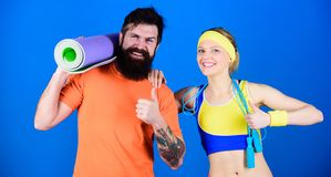 Man and woman exercising with yoga mat and jump rope. Fitness exercises. Workout and fitness. Girl and guy live healthy stock photography