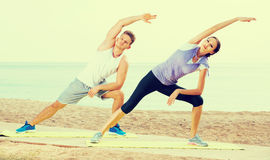 Man and woman exercising yoga poses standing. Man and women exercising yoga poses standing on sunny beach by sea in morning Stock Images