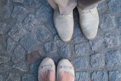Man and woman face to face stand on cobbles. Focus on the footwear. Rendezvous concept stock photos