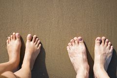 Man and woman feet standing on sandy brown beach. Top view Stock Photos