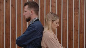 Man and woman in a fight. Offended man and woman standing back to back outside by building. Young couple in a big fight. Boyfriend and girlfriend are frustrated stock video footage