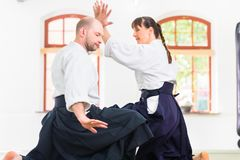Man and woman fighting at Aikido martial arts school stock image
