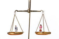 Man and Woman Figurines on Scales Royalty Free Stock Image