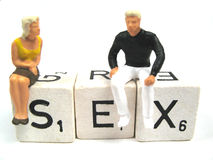 Man and woman figurines on the spelled word sex. Two figurines on the word sex stock photos