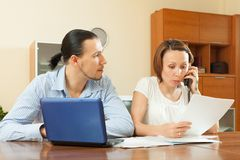 Man and woman with financial document. Serious middle-aged Man and women looking financial document at home Stock Images
