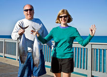 Man and Woman With Fish. A man and woman learning to fish and very happy with the catch Stock Image