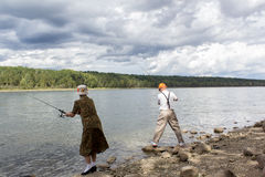 Man and woman fishing. Man and women fishing by a lake Royalty Free Stock Photos