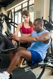 Man And Woman Fitness Exercise. Man and woman exercising together at a fitness center on a stationary bicycle exercise machine.  Woman could be a personal Royalty Free Stock Photos