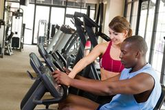 Man And Woman Fitness Exercise. Man and woman exercising together at a fitness center on a stationary bicycle exercise machine.  Woman could be a personal Royalty Free Stock Photography