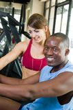 Man And Woman Fitness Exercise. Man and woman exercising together at a fitness center on a stationary bicycle exercise machine.  Woman could be a personal Stock Image