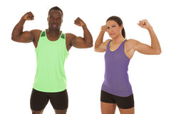 Man an woman fitness flex. A men and women flexing their muscles with a serious expression on their faces royalty free stock image