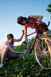 Man and Woman Fixing a Bike - Vertical Stock Photo