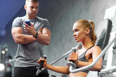 Man and woman flexing muscles on gym machine Stock Image