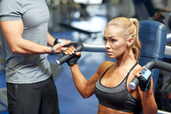 Man and woman flexing muscles on gym machine. Sport, fitness, bodybuilding, teamwork and people concept - young women and personal trainer flexing muscles on gym Royalty Free Stock Photo