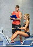 Man and woman flexing muscles on gym machine Stock Images