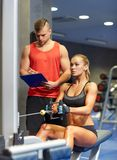 Man and woman flexing muscles on gym machine Stock Photography