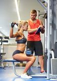 Man and woman flexing muscles on gym machine Royalty Free Stock Photos