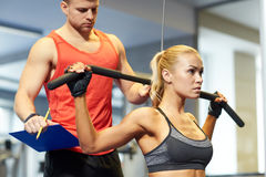 Man and woman flexing muscles on gym machine Royalty Free Stock Photography