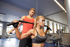 Man and woman flexing muscles on gym machine Royalty Free Stock Photo