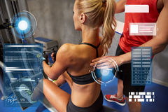 Man and woman flexing muscles on gym machine Stock Photos