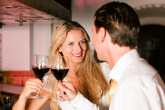Man and woman flirting in hotel bar. Man and woman in a hotel bar in the evening having glasses of red wine and a little flirt stock image