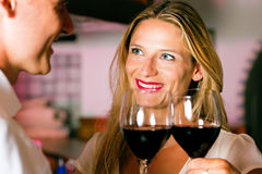 Man and woman flirting in hotel bar. Man and woman in a hotel bar in the evening having glasses of red wine and a little flirt stock photography